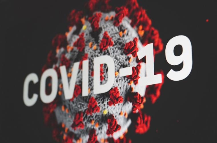 A coronavirus against a black backdrop with the copy COVID-19 in white in front of it