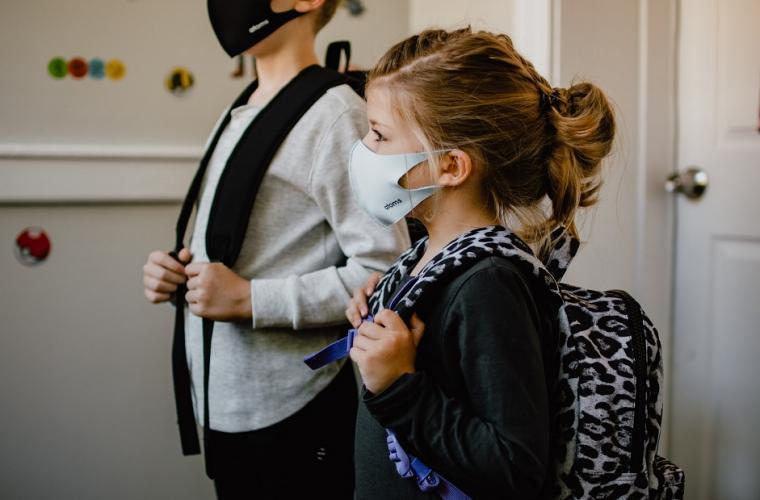 school boy and girl wearing uniform and face mask